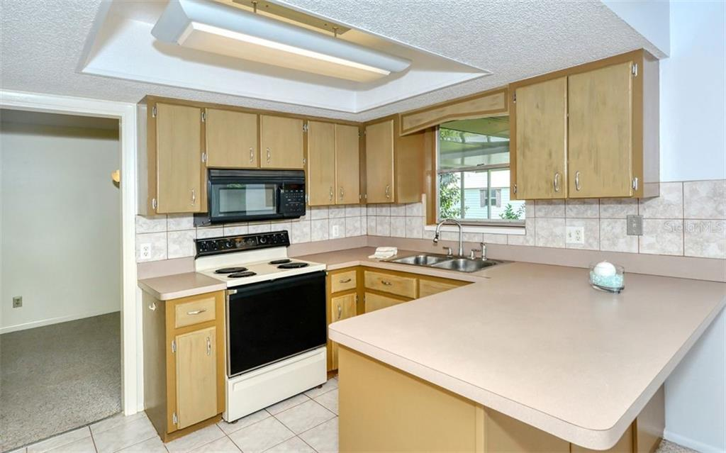 The kitchen features a closet panty, breakfast bar and lots of cabinets for extra storage - Single Family Home for sale at 3286 Jamestown St, Port Charlotte, FL 33952 - MLS Number is A4444310