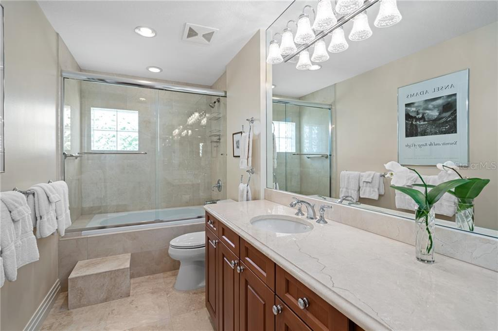 Guest Bathroom with the finest of finishes...walnut cabinetry, Travertine tile and granite countertops. - Condo for sale at 401 S Palm Ave #402, Sarasota, FL 34236 - MLS Number is A4446224