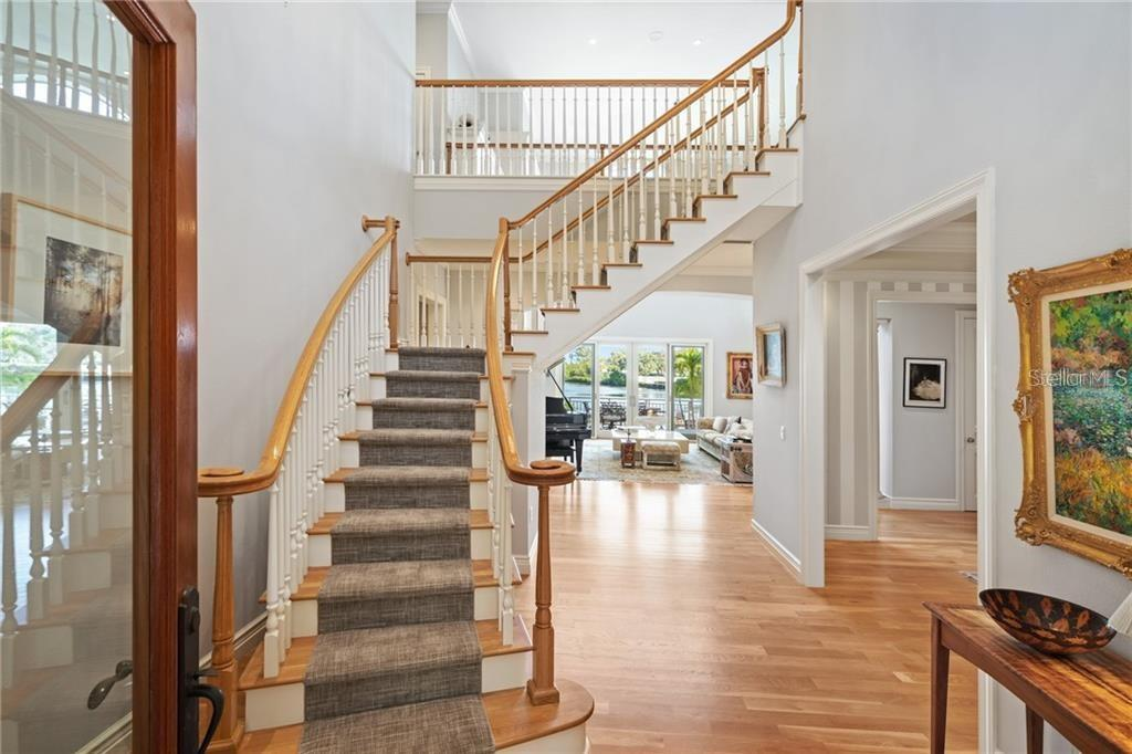 Grand oak staircase. A second staircase is positioned in the rear of the home. - Single Family Home for sale at 711 Mangrove Point Rd, Sarasota, FL 34242 - MLS Number is A4447637