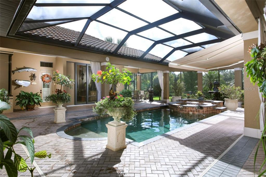 Pool as set up by Seller looking toward the separate guest suite; the retractable awning is open - Single Family Home for sale at 15212 Linn Park Ter, Lakewood Ranch, FL 34202 - MLS Number is A4450793