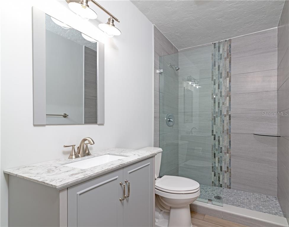 Guest bathroom with custom walk-in shower - Single Family Home for sale at 5057 Bell Meade Dr, Sarasota, FL 34232 - MLS Number is A4461883