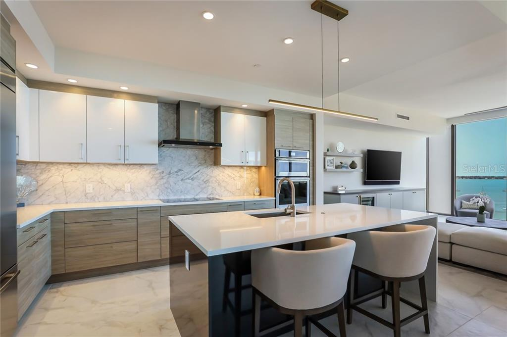 JennAir appliances are featured in the kitchen, with an induction stovetop, convection ovens, and thoughtful storage. - Condo for sale at 1155 N Gulfstream Ave #1404, Sarasota, FL 34236 - MLS Number is A4467921