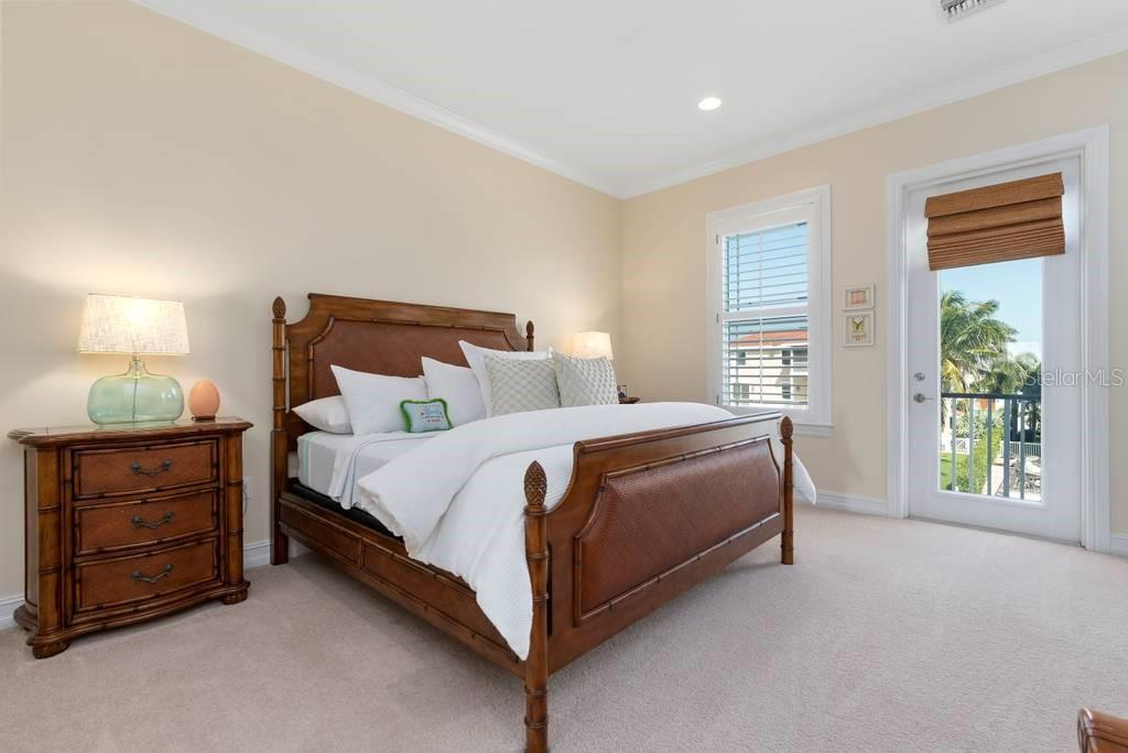 Second master bedroom with private balcony overlooking pool and canal - Single Family Home for sale at 605 N Point Dr, Holmes Beach, FL 34217 - MLS Number is A4469001