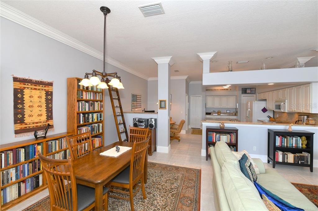 The dining room and kitchen.  Substitute stools for the book cases and create a breakfast bar. - Villa for sale at 4590 Samoset Dr, Sarasota, FL 34241 - MLS Number is A4471881