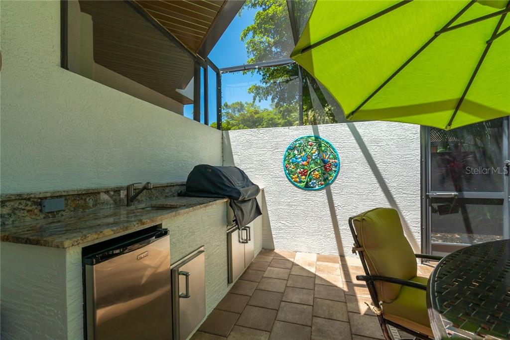 Oudoor Kitchen with grill, sink, and refrigerator. - Single Family Home for sale at 1907 Clematis St, Sarasota, FL 34239 - MLS Number is A4474600