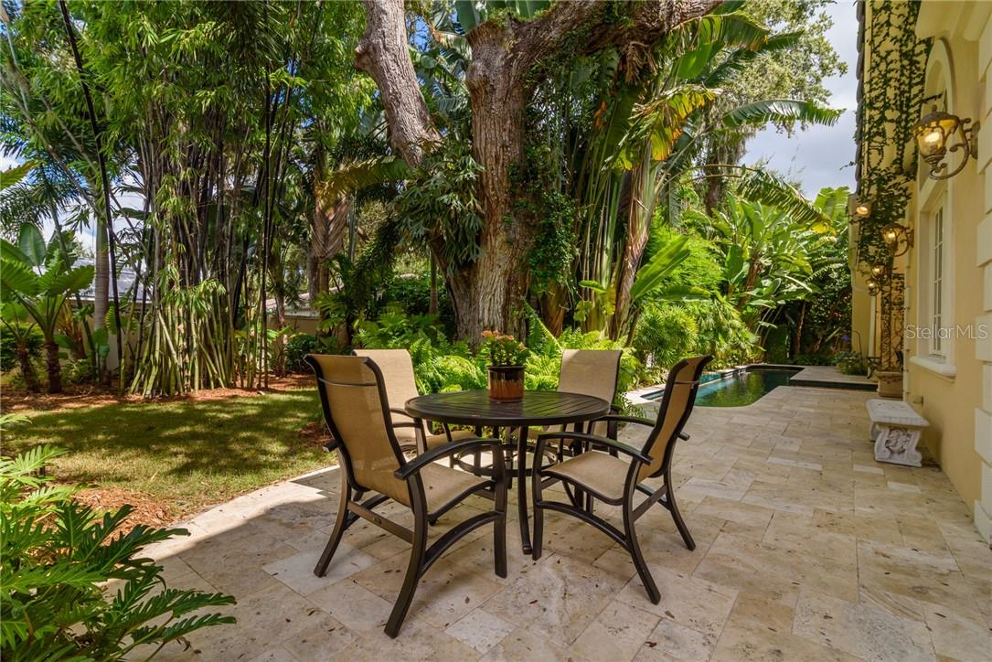 Divinely landscaped tropical rear gardens feature rich plantings and separate patio with travertine flooring for dining al fresco. - Single Family Home for sale at 1807 Oleander St, Sarasota, FL 34239 - MLS Number is A4475067