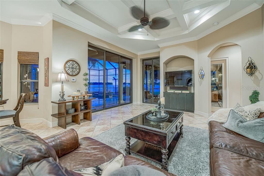 Family room with sliders to the lanai and custom molding ceiling detail - Single Family Home for sale at 14507 Leopard Crk, Lakewood Ranch, FL 34202 - MLS Number is A4478709