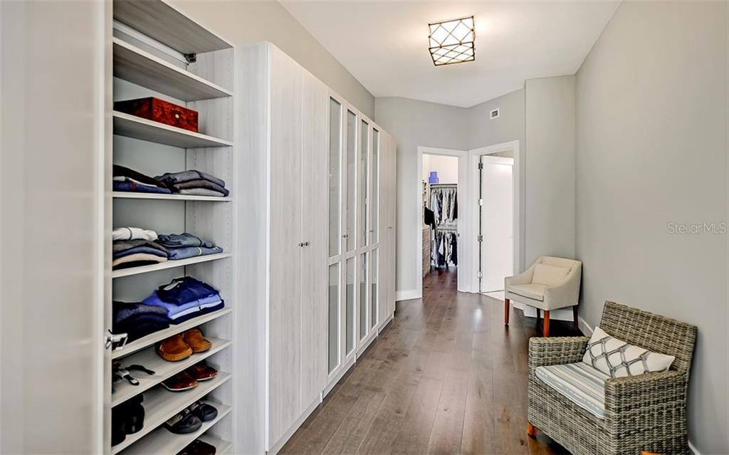 The large dressing area with custom cabinets leads to a large walk-in closet and the ensuite bath - Condo for sale at 1155 N Gulfstream Ave #1701, Sarasota, FL 34236 - MLS Number is A4480090