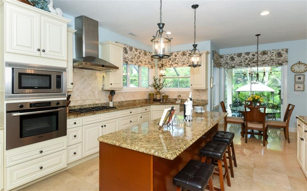 The kitchen is a Chef's dream! This kitchen boasts a gas range top, wall oven & microwave, solid wood cabinetry, granite countertops, pull out shelving in all lower cabinets, wine refrigerator, soft close drawers and plenty of storage and service space! - Single Family Home for sale at 1603 Landfall Dr, Nokomis, FL 34275 - MLS Number is A4480987