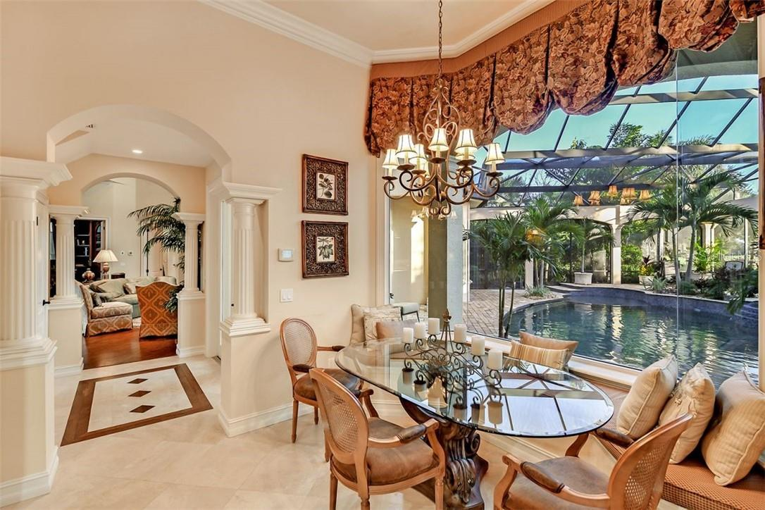 The kitchen vestibule with inlaid wood & marble motif flooring, the aquarium window makes you feel like you are outside, note the classical columns & arches to add some architectural style. - Single Family Home for sale at 8263 Archers Ct, Sarasota, FL 34240 - MLS Number is A4483993