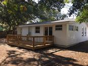 Enjoy the shaded backyard from the wooden deck. - Single Family Home for sale at 938 Highland St, Sarasota, FL 34234 - MLS Number is A4186423