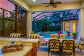 Outdoor Kitchen looks out onto the covered dining patio, pool and preserve. - Single Family Home for sale at 13223 Palmers Creek Ter, Lakewood Ranch, FL 34202 - MLS Number is A4408290