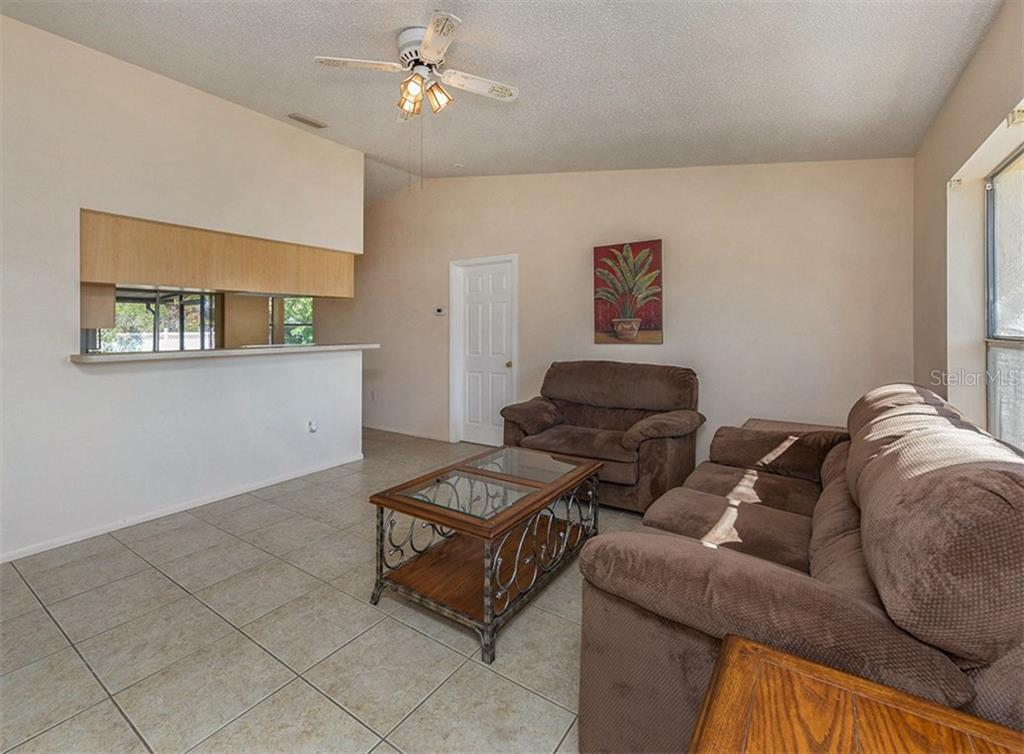 Living Room to Kitchen - Single Family Home for sale at 10308 Grail Ave, Englewood, FL 34224 - MLS Number is N5911429