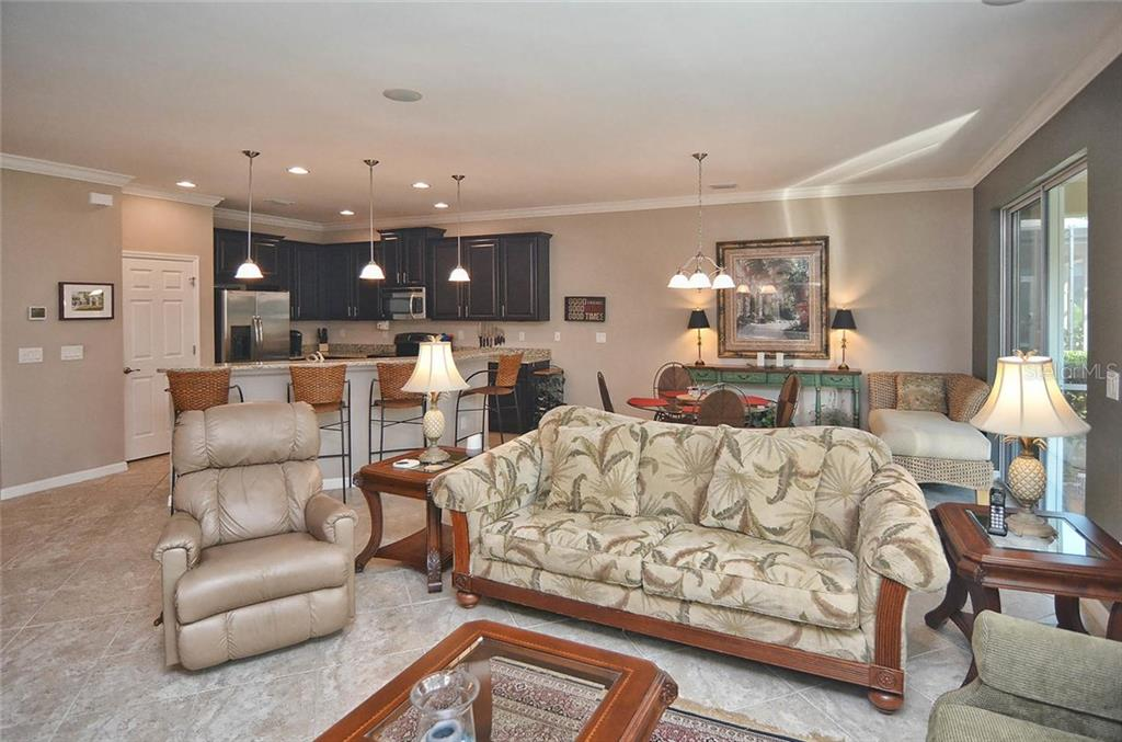 Living room, kitchen, dinette - Single Family Home for sale at 9124 Coachman Dr, Venice, FL 34293 - MLS Number is N5914408