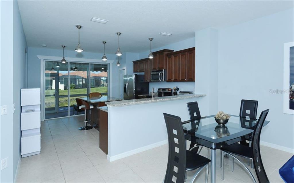 Dining Room and Kitchen - Villa for sale at 10889 Lerwick Cir, Englewood, FL 34223 - MLS Number is N5916198