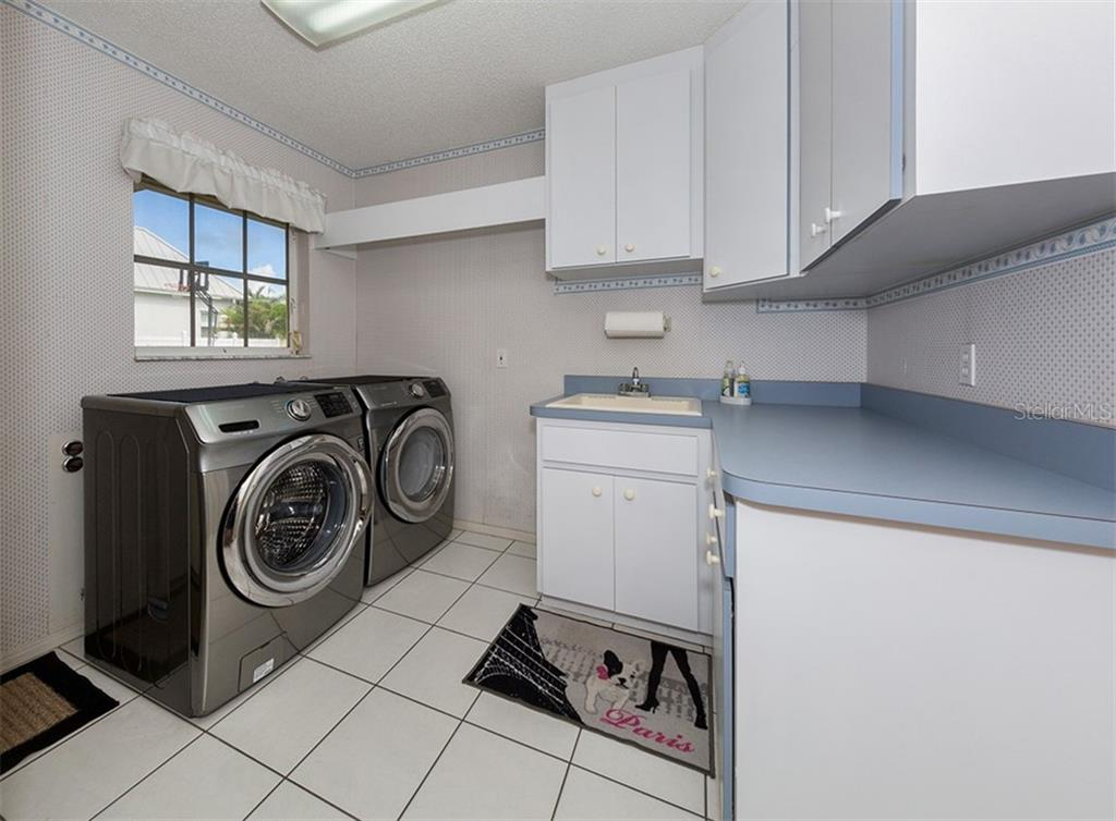 Large laundry room with newer washer and dryer, plenty of closet and storage space, located off of the kitchen. - Single Family Home for sale at 620 Valencia Rd, Venice, FL 34285 - MLS Number is N6100912