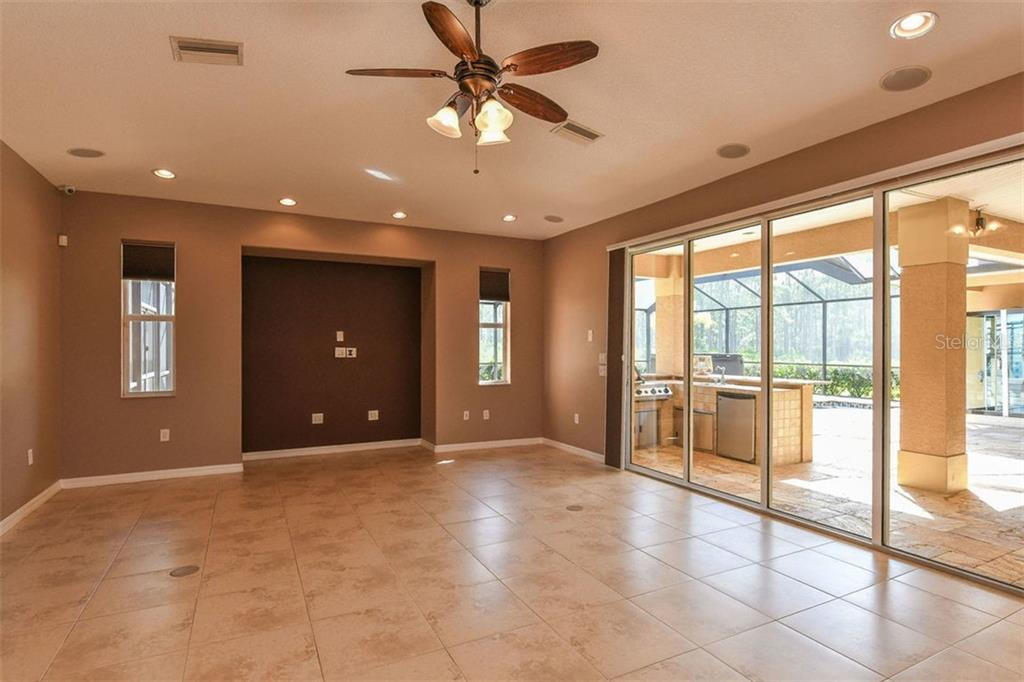 Family room with sliders to outdoor kitchen, lanai and pool - Single Family Home for sale at 9150 Deer Ct, Venice, FL 34293 - MLS Number is N6101408