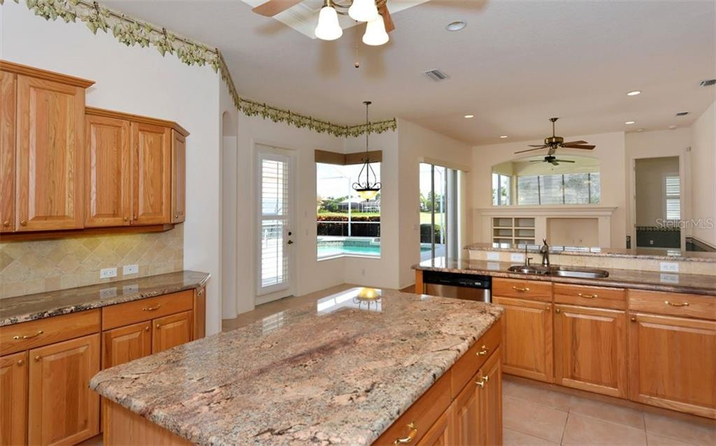 Kitchen - to breakfast room (aquarium window) - Single Family Home for sale at 969 Chickadee Dr, Venice, FL 34285 - MLS Number is N6102722