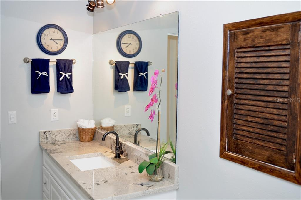 The guest bathroom vanity has brand new level 4 granite, a new bronze jacuzzi faucet, a new rectangle sink, and a new bronze light fixture above. - Single Family Home for sale at 1656 La Gorce Dr, Venice, FL 34293 - MLS Number is N6107911