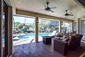 Covered lanai area overlooking pool. - Single Family Home for sale at 2560 Pebble Creek Pl, Port Charlotte, FL 33948 - MLS Number is N6109100