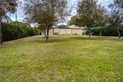 View from the backyard, with plenty of room for games, gardening, or additional toys. - Single Family Home for sale at 1670 Maria St, Englewood, FL 34223 - MLS Number is N6113779