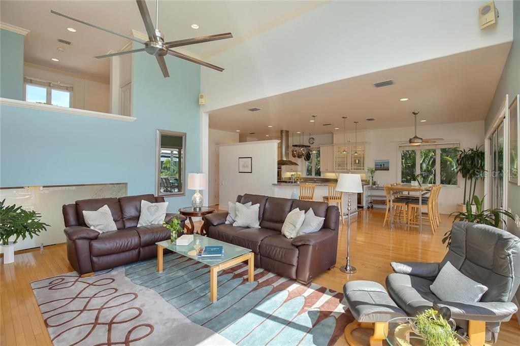 Warm Oak Wood Floors, White Cabinetry unites the Breakfast Area, Great Room and Spacious Deck overlooking the Water. - Single Family Home for sale at 722 Siesta Dr, Sarasota, FL 34242 - MLS Number is A4169257