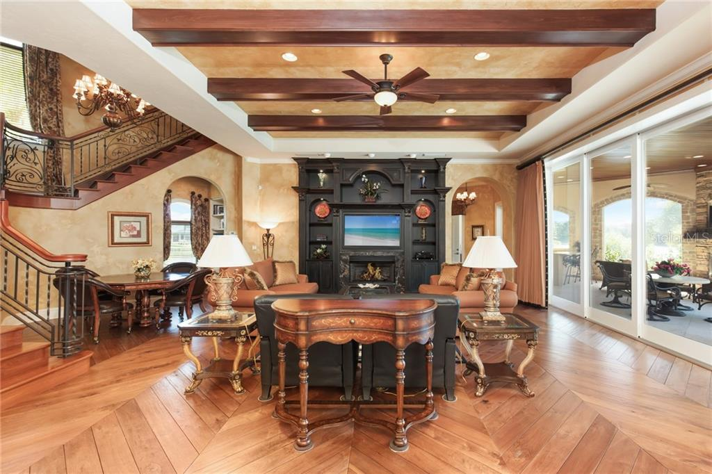 Family room includes pocket sliding doors to screened summer kitchen and patio, walnut wood flooring, gas fireplace, exposed wood beams and staircase landing to upstairs game room and theater. - Single Family Home for sale at 7320 Barclay Ct, University Park, FL 34201 - MLS Number is A4200908