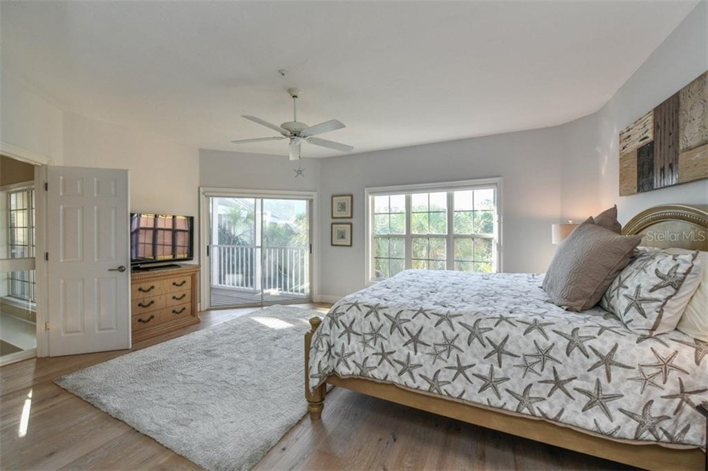 Large master bedroom with coastal flooring and access to the private balcony. - Single Family Home for sale at 3947 Somerset Dr, Sarasota, FL 34242 - MLS Number is A4201541