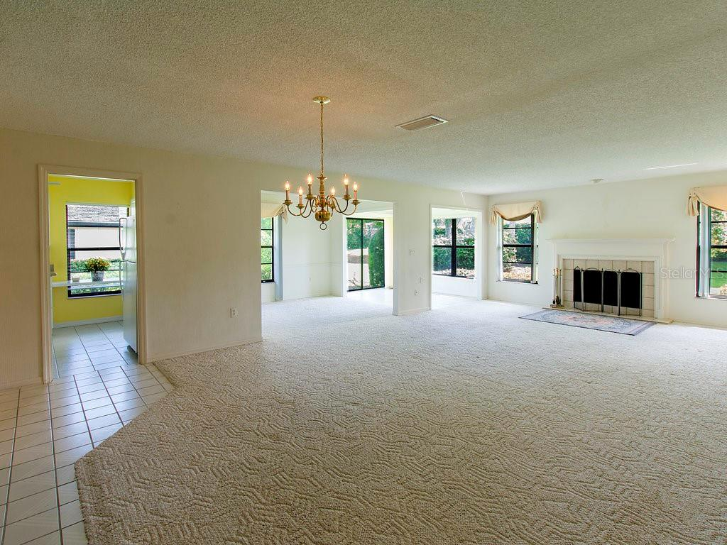 Open space concept. Living room with wood burning fireplace. Light and bright. - Villa for sale at 7467 Carnoustie Dr #5d, Sarasota, FL 34238 - MLS Number is A4412518