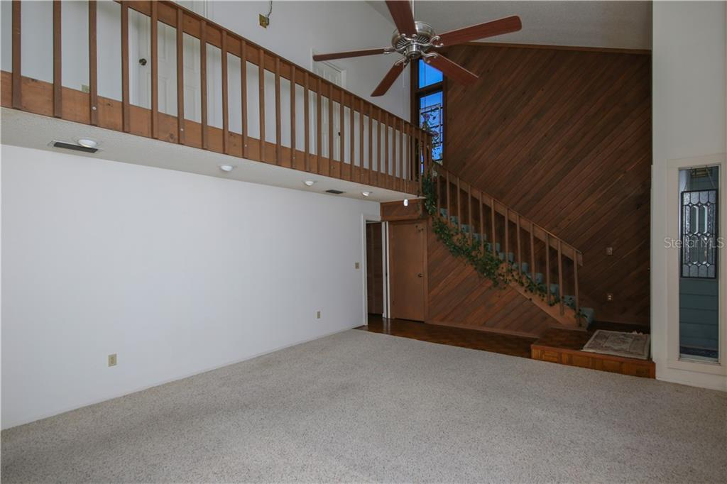 Stairs lead to 2 additional large bedrooms w/balcony overlooking living room - Single Family Home for sale at 7611 Alhambra Dr, Bradenton, FL 34209 - MLS Number is A4434753