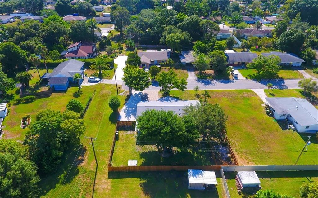 Aerial shows the backyard view, county easement north of the home gives a buffer between neighbors. - Single Family Home for sale at 120 23rd Street Ct Ne, Bradenton, FL 34208 - MLS Number is A4438232
