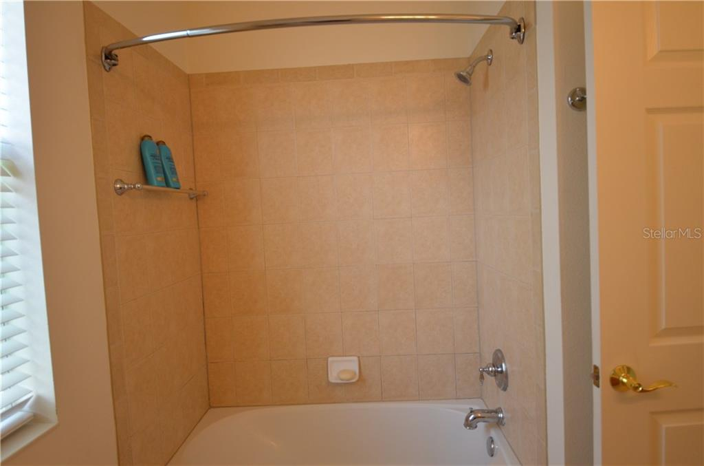 Guest bathroom has tiled shower, linen closet, tile floors, tub shower combo. - Single Family Home for sale at 3632 Summerwind Cir, Bradenton, FL 34209 - MLS Number is A4438762