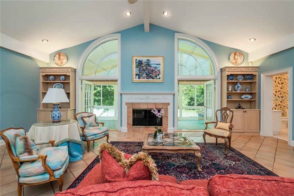 The Family room hosts a cozy fireplace between two sets of double French doors that lead to the lovely Solarium which overlooks the lake and lush Floridian backdrop! - Single Family Home for sale at 3702 Beneva Oaks Blvd, Sarasota, FL 34238 - MLS Number is A4438878